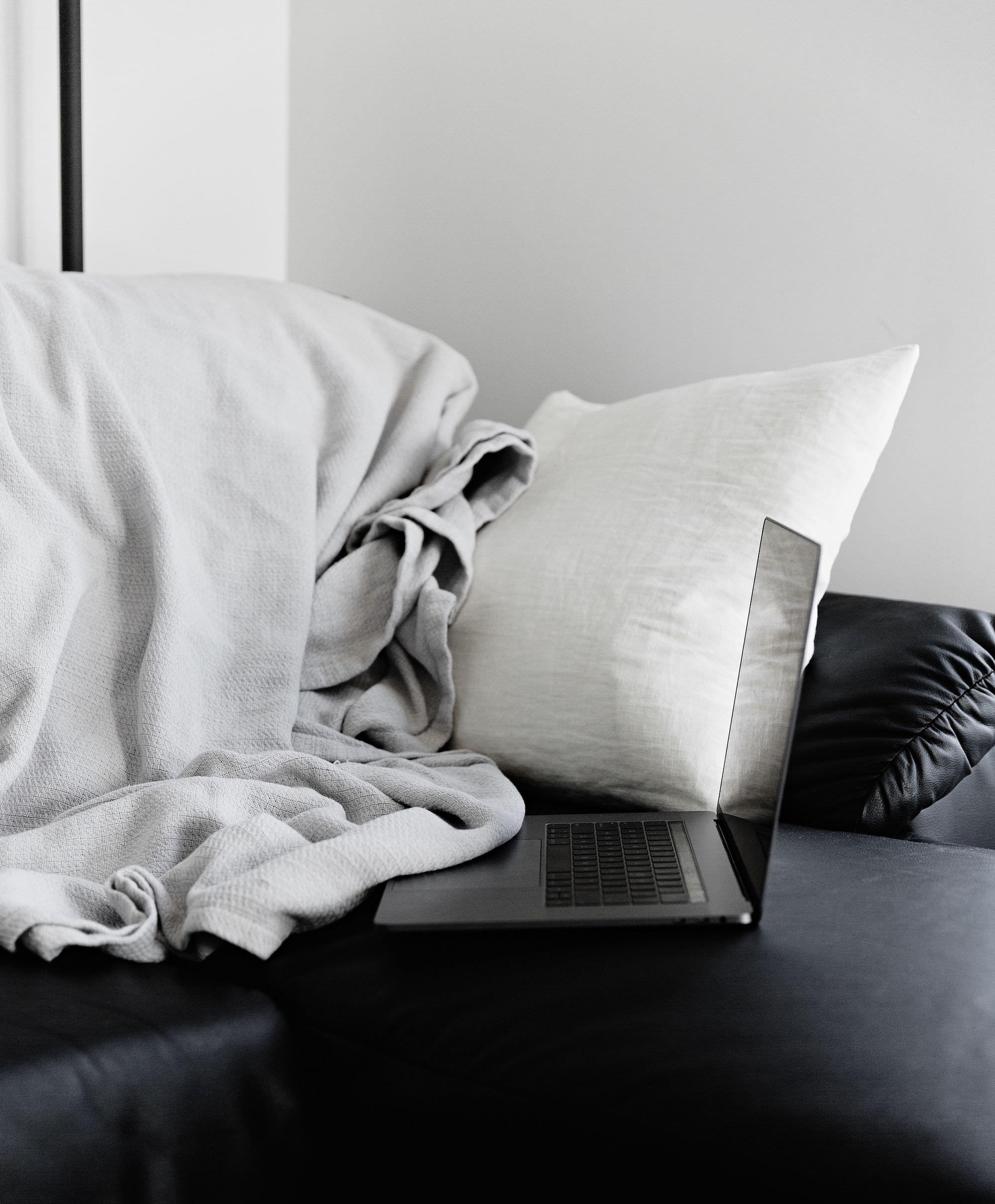 Ordinateur portable sur un lit avec oreiller et draps.