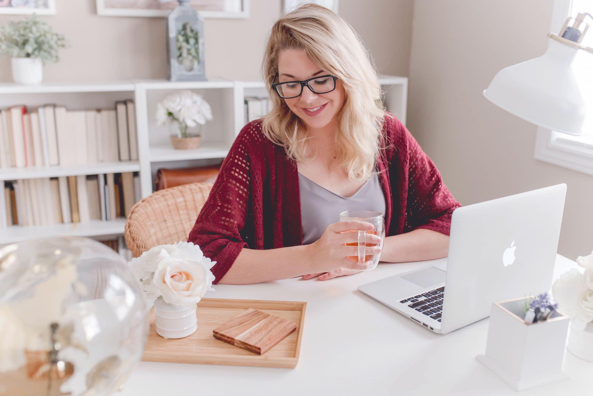 Femme tenant une tasse de thé devant un ordinateur portable dans un bureau à domicile.